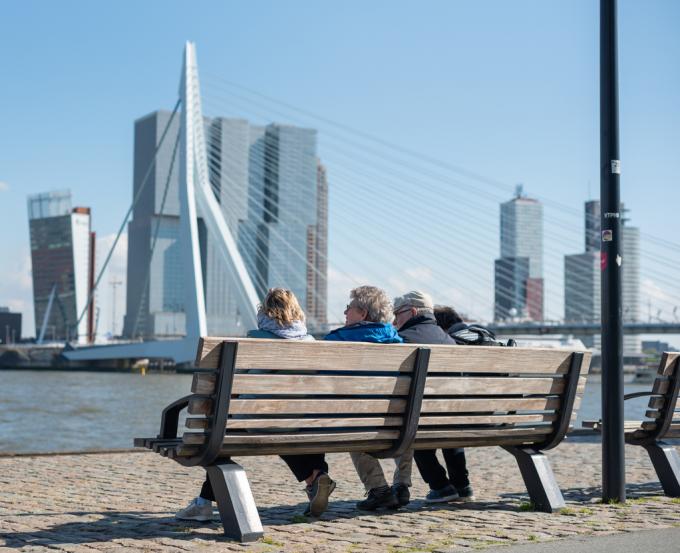 Mensen op een bankje kijken vanaf de kade naar de Erasmusbrug.